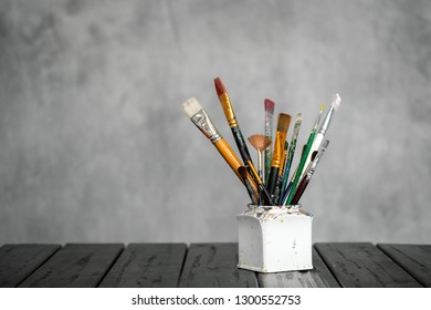 Artist's tools, brushes, paints and a palette lie on a black wooden table on a gray fabric background. Copy space for text.