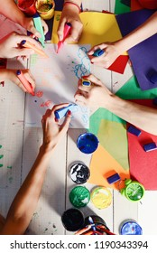 Artists wooden table with paints and colored paper. Art and artwork concept. Hands hold colorful markers and draw. Markers in male and female hands draw cute drawings on white paper