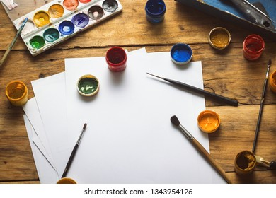 The artist's workplace with watercolor paints, gouache, brushes and sheets of paper on a wooden background. Copy space. Flat lay, top view