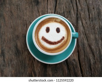 The arts of a cup of coffee, Cappucino with smile face on dark wooden.