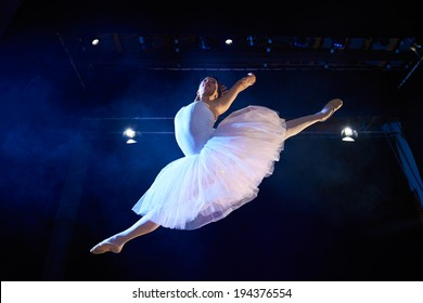 Arts and entertainment in theatre with female classic dancer in tutu, jumping high on stage during performance