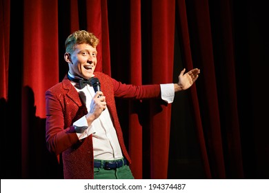 Arts and entertainment in theatre with funny man working as anchorman, standing against red curtains with microphone