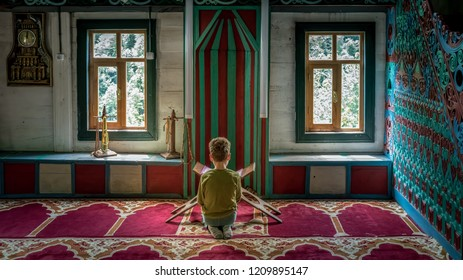 Artvin, Turkey - July 2018: Unidentified boy praying inside the colorful decoration of the mosque in iremit maral village in Artvin, Turkey