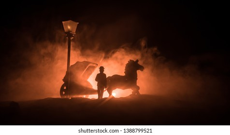 Artwork decoration. Silhouette of old coach with horse on dark toned foggy background. Selective focus