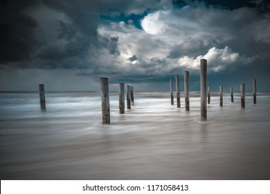 Artwork near the coastal city 'hats' in the Netherlands. A floating cloud of air with a counter-light and misty sea. Beach with sunny weather during a summer storm