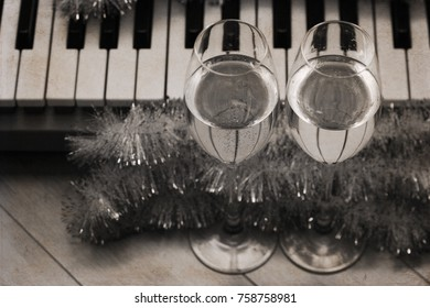 Artwork in vintage style, reflection of piano keys in two wine glasses, pianoforte, Christmas decoration/ monochrome