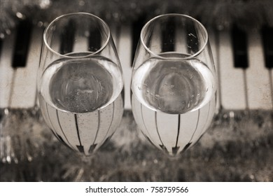 Artwork in vintage style, reflection of piano keys in two wine glasses, pianoforte, Christmas decoration/ monochrome image