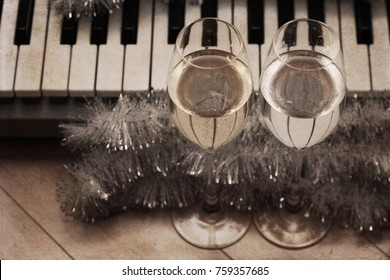 Artwork in vintage style, reflection of piano keys in two wine glasses, pianoforte, Christmas decoration