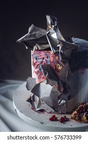 Artwork. Wedding cake decorated in loft style, decorated with metal plates and red fading. on a background of wavy fabric. food design. trends