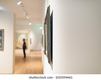 Artworks on white wall in museum room with visitor blurred in background.