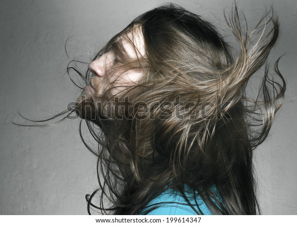 Arty portrait of a fashionable male model with long hair over dark gray background. studio shot