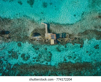 Aruba aerial of shack surrounded by crystal clear ocean