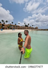 Aruba Caribbean couple man and woman mid age on vacation on the beach with palm trees on the beach