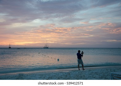 Aruba, Caribbean - September 25, 2012: Photographer at the Sunset with anchored sail boats on sea by the bay. The image was taken in Aruba, in the Caribbean Sea.
