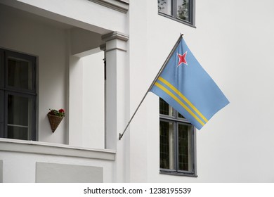 Aruba flag hanging on a pole in front of the house. National flag waving on a home displaying on a pole on a front door of a building and raised at a full staff.