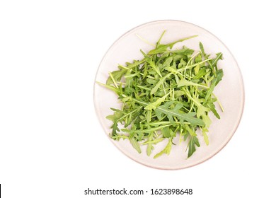 Arugula leaves on a plate isolated on a white background, dandelion, rucola salad