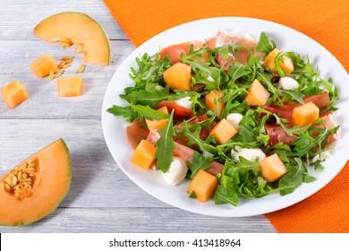 Arugula, prosciutto, mozzarella and melon  salad on a white dish, close up, view from above