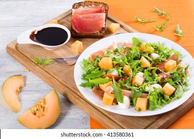 Arugula, prosciutto, mozzarella and melon salad  on dish, balsamic vinegar in gravy boat and prosciutto sandwich  on wooden  cutting board , top view