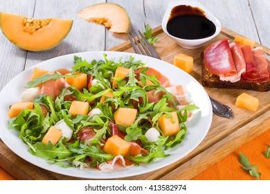 Arugula, prosciutto, mozzarella salad and melon on a white dish on a wooden table, top view