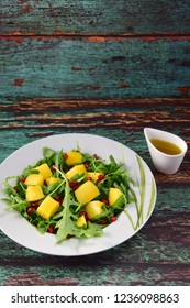Arugula salad with mango and pomegranate served with olive oil dressing