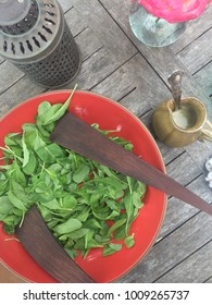 Arugula salad in orange ceramic bowl on wooden table with dressing