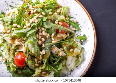 Arugula salad with pine nuts, cherry tomatoes and cheese. Top view