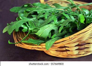 Arugula salad  in a wicker basket on dark background. Close up of fresh green healthy food. Diet concept