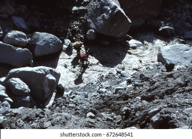 ARUN VALLEY, NEPAL - OCT 17, 1987 - Porters carrying loads across river,Arun Valley,  Himalyas, Asia