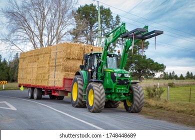 Arundel, Canterbury, New Zealand, June 3 2020: A farm tractor shifts a trailer load of straw bales along a country road in winter for stock feed