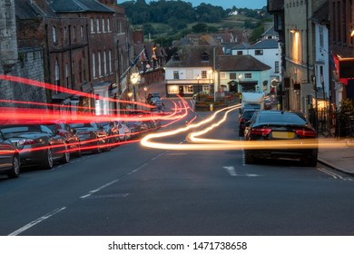 Arundel High Street, England, at night with car light trails. Arundel is a popular tourist attraction with a beautiful castle and impressive cathedral.