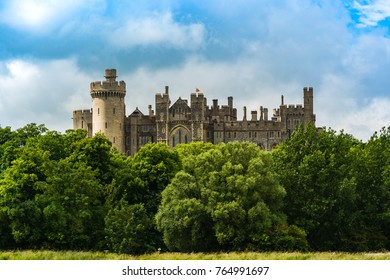 Arundel, UK: Panoramic view of the Arundel Castle surrounded by a green forest, a restored and remodeled medieval castle.