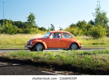 ARUNDEL, WEST SUSSEX, UK, 5TH AUGUST 2018 - Orange vintage Volkswagon Beetle car on the road