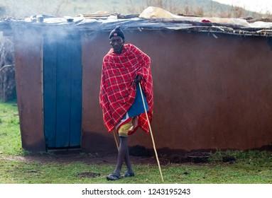 ARUSHA, TANZANIA - AUGUST 10: masai man in front of his hut in a reserve august 10, 2014 in Arusha, Tanzania