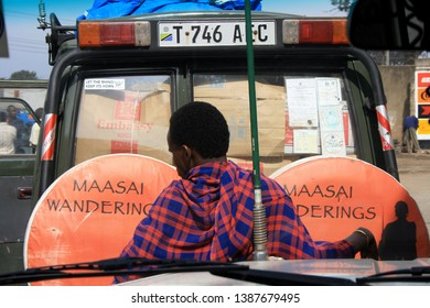 ARUSHA, TANZANIA - AUGUST 2008: portrait of a Masai man waiting outside a safari Jeep ready to start the tour in Arusha, Tanzania