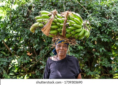 Arusha, Tanzania - december 24, 2019 : African old woman on the street with green bananas on head near home in Arusha, Tanzania, East Africa, close up