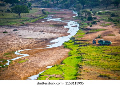 ARUSHA, TANZANIA - January 2018: Aerial view of the forest and river in Tarangire National Park. Jeep cars in Tanzania National Park.