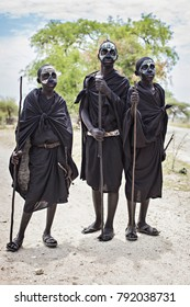 ARUSHA, TANZANIA - January 2018: Three young Masai warriors with traditional black and white face painting and black clothes, Arusha, Tanzania