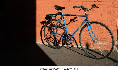 Arvada, CO / USA - November 14, 2018: Vintage blue Trek bicycle in city setting against red brick wall with dramatic shadows