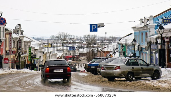 ARZAMAS, RUSSIA - JANUARY 3, 2015. Winter cityscape of road full of cars, small buildings in line and bare trees in the skyline