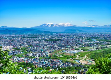 Asahikawa city, summer cityscape and daisetuzan mountain range. hokkaido, japan