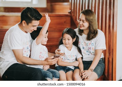 Asain family play game at home - father and Mather teach son and daughter on smartphone