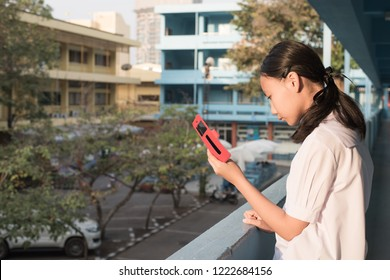Asain high school girl play smartphone in morniing time