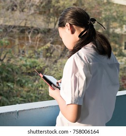 Asain high school girl play smartphone in morniing time