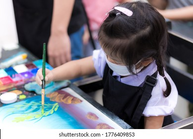 Asain little child girl wearing a white cloth mask is learning to draw art with watercolor and brush. Adorable kid wore a black apron sitting to draw pictures. Child 3 years old.
