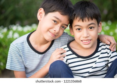 Asain Sibling boy sit togehter in the park