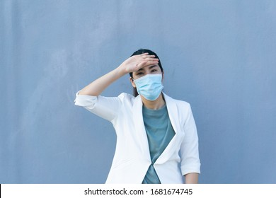 Asain woman with mask worry if she has fever or not