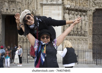 Asain women mother and daughter travel and posing for take photo with Cathedrale Notre-Dame de Paris in Paris, France