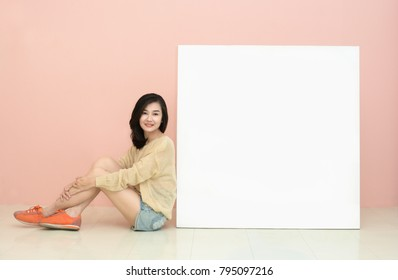 Asain young woman leaning against white board