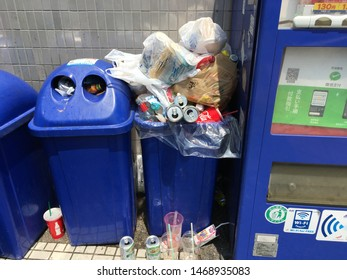 Asakusa, Tokyo, Japan - August, 23, 2019 - Blue recycle rubbish bin, garbage can overflowing with soda cans. Tourists are often confounded by Japan lack of public rubbish bins, garbage cans.