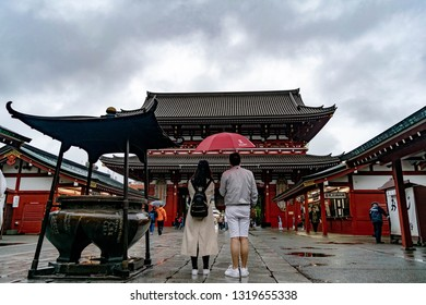 Asakusa, Tokyo, Japan - June 13 2016 - Senso-ji Temple, a couple stand in front of the temple after making offerings and praying.